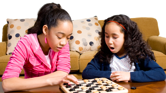 Two young girls playing a board game